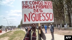 "FILE - A man holds a placard reading, ""Congo is not the property of Nguesso,"" during a demonstration against President Denis Sassou Nguesso in Brazzaville, Republic of Congo, Sept. 27, 2015."