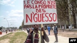 """FILE - A man holds a placard reading, """"Congo is not the property of Nguesso,"""" during a demonstration against President Denis Sassou Nguesso in Brazzaville, Republic of Congo, Sept. 27, 2015."""
