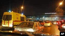Vehicles are seen in front of Domodedovo airport in Moscow, Monday, Jan. 24, 2011. An explosion ripped through the international arrivals hall at Moscow's busiest airport on Monday, killing dozens of people and wounding scores, officials said. The Russian