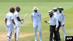 سری لنکن کپتان چندی مل امپائر علیم ڈار کے ہاتھ میں بال کو دیکھ رہے ہیں