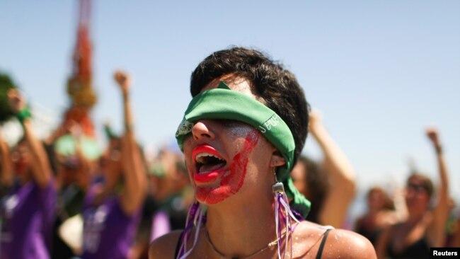 """Una manifestante en un grupo brasileño de mujeres hace un gesto mientras canta la canción """"El violador eres tú"""", que se hizo famosa en Chile. La marcha es con motivo del Día Internacional de la Mujer en Río de Janeiro, Brasil, el 8 de marzo de 2020."""