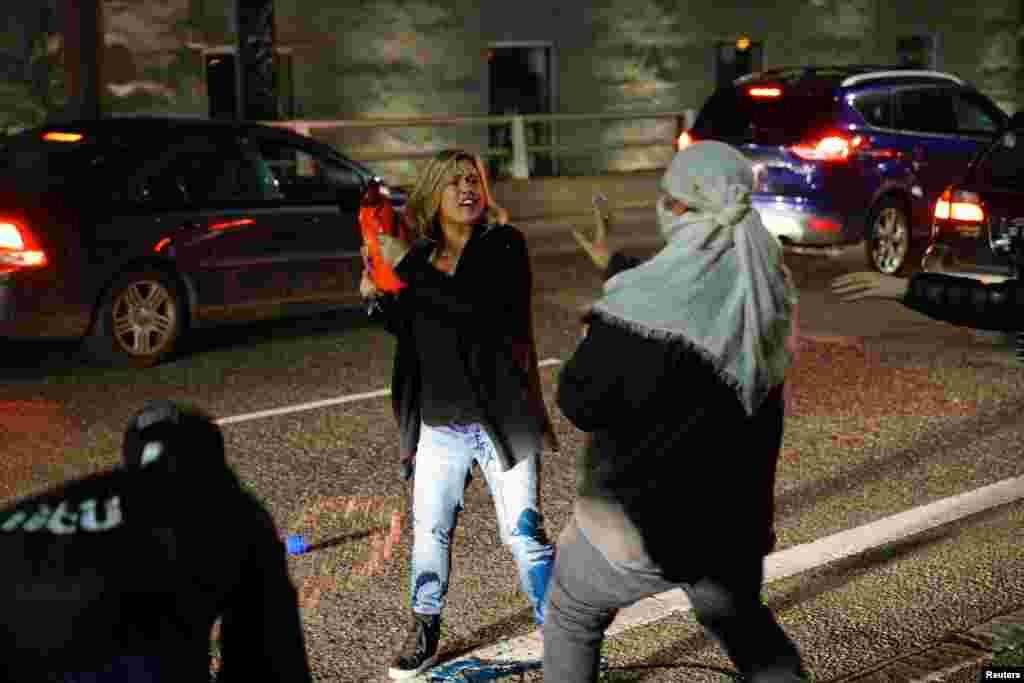 A motorist who was caught in the middle of a riot threatens a demonstrator with detergent during a protest against the election of Republican Donald Trump as president of the United States in Portland, Oregon, Nov. 10, 2016.