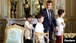 French President Emmanuel Macron holds the hand of a boy with autism as they visit the Elysee Palace before the launching of a program to enhance the diagnosis and treatment of autism, in Paris, July 6, 2017. Macron will unveil a plan to help children with autism.