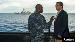 U.S. Secretary of Defense Ash Carter (R) speaks with U.S. Navy Cmdr. Robert C. Francis Jr., as Carter and Malaysian Defense Minister Hishammuddin Hussein (not pictured) visited the USS Theodore Roosevelt aircraft carrier in the South China Sea, in this handout image, Nov. 5, 2015.
