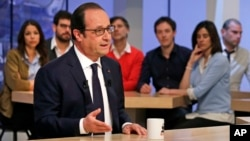 French President Francois Hollande gestures as he takes part in a live television program at Canal+ headquarters in Paris, April 19, 2015.