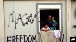 在希臘伊多梅尼島的一個庇護所裡一名婦女懷抱兒童站在窗前。