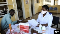 A patient waits for his pills as he meets with a nurse in Swaziland.