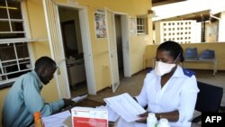 FILE - A patient waits for his pills as he meets with a nurse at Nhlangano health center in Swaziland, Oct. 28, 2009.