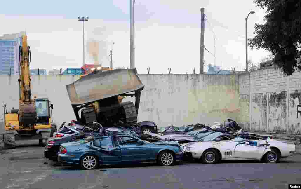 A bulldozer destroys smuggled luxury cars worth 61,626,000.00 pesos (approximately $1.2 million), which include used Lexus, BMW, Mercedes-Benz, Audi, Jaguar and Corvette Stingray, during the 116th Bureau of Customs founding anniversary in Metro Manila, Philippines