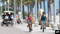 FILE -- Riders along the Hollywood Beach Broadwalk, in Florida, which was the most popular destination for home buyers who moved out of state in 2018.