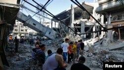 巴勒斯坦人聚集在一座倒塌的清真寺尖塔旁. 警方说, 以色列7月30日对加沙地带的空袭摧毁了这座清真寺.