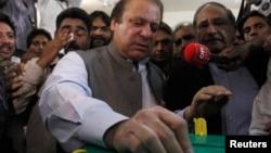 Nawaz Sharif, pemimpin partai politik Liga Muslim Pakistan- Nawaz (PML-N) memasukkan surat suaranya di kotak suara di salah satu TPS di Lahore (11/5).