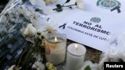 "A sign that reads ""No to terrorism, Colombia is in mourning"" is seen in front of the scene where a car bomb exploded, in Bogota, Colombia, Jan. 18, 2019."