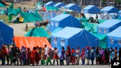 Ljudi stoje u redu za pijaću vodu u kampu u Katmanduu, gde su privremeno smešteni jer su im kuće uništene u zemljotresu