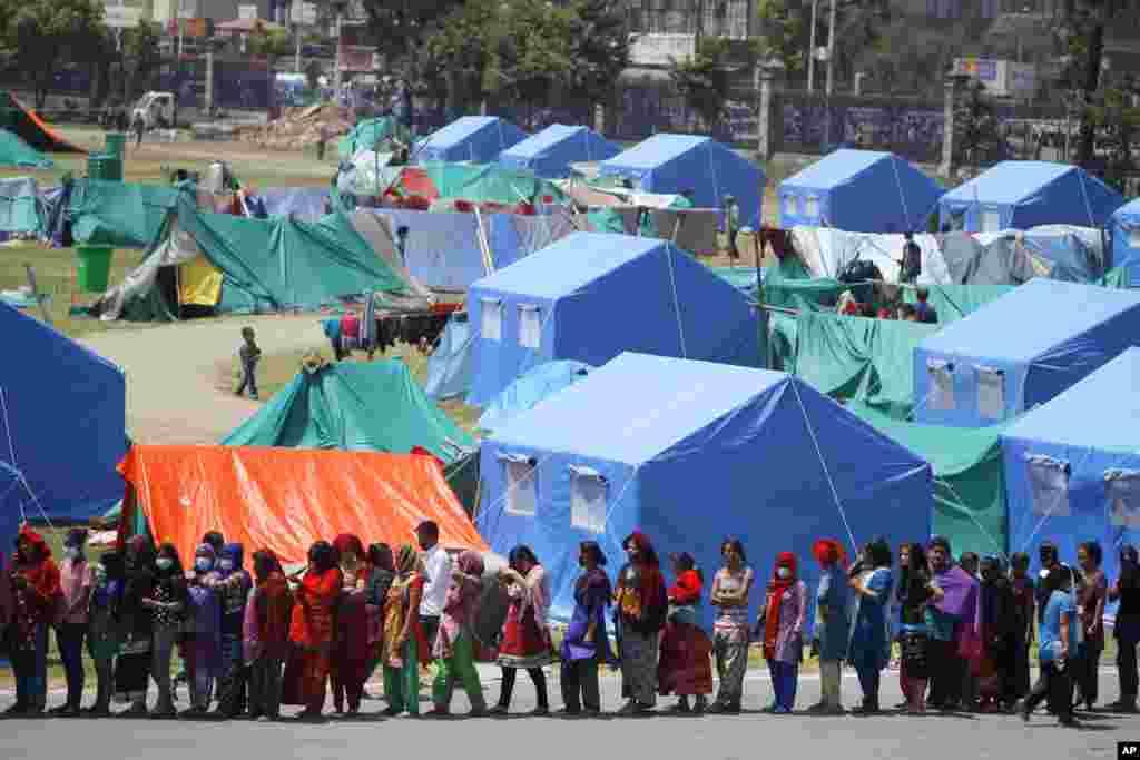 آوارگان، در اردوگاهی در پایتخت نپال در صف آب و غذا ایستاده اند.