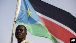 A Bari, un habitant agite un drapeau sud-soudanais le 8 juillet 2011