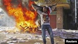 Un manifestante celebra el asalto a una oficina de la Hermandad Musulmana en Alejadría, Egipto, mientras continúan las protestas contra el presidente Mohamed Morsi.