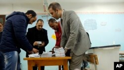 Election workers count ballots at the end of three-day vote of the referendum on constitutional amendments at polling station in Cairo, Egypt, Monday, April 22, 2019.