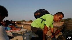 """Un migrante centroamericano sube al techo de un tren de carga, de camino a la frontera de EE.UU. con México, en Ixtepec, estado de Oaxaca, México, el 23 de abril de 2019. El tren es conocido como """"La Bestia""""."""