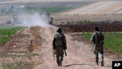 FILE - Turkish soldiers patrol near the border with Syria, outside the village of Elbeyli, east of the town of Kilis, southeastern Turkey, July 24, 2015.