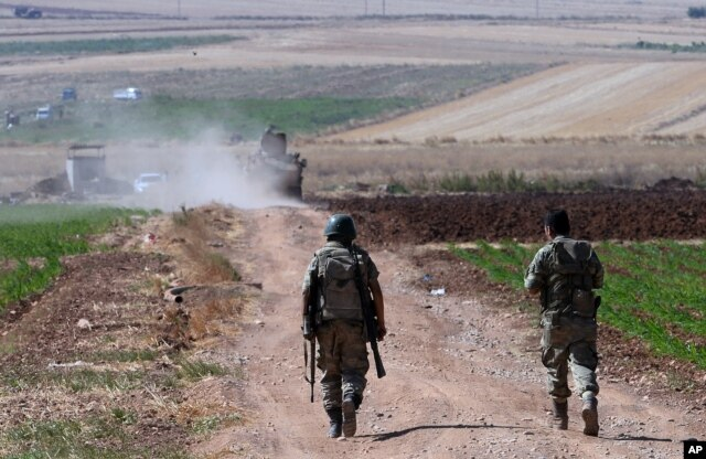 FILE - Turkish soldiers patrol near the border with Syria, ouside the village of Elbeyli, east of the town of Kilis, southeastern Turkey, July 24, 2015.