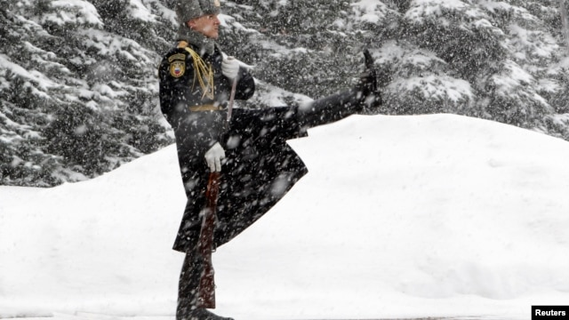 An honor guard marches during the changing of the guards ceremony at the Tomb of the Unknown Soldier by the Kremlin wall during snowfall in central Moscow, Mar. 25, 2013.