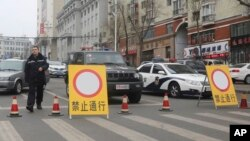 FILE - Police vehicles block a street of the prefectural seat of Shuangyashan after several days of protest by miners over late wages in northeastern China's Heilongjiang province. Frustration among miners over unpaid wages has swelled to the brink of unrest in the province in China's far northeast. (AP Photo/Gerry Shih) Police vehicles block a street of the prefectural seat of Shuangyashan after several days of protest by miners over late wages in northeastern China's Heilongjiang province. Frustration among miners over unpaid wages has swelled to the brink of unrest in the province in China's far northeast.