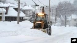 Una pala mecánica remueve la nieve en Marlborough, Massachusetts donde se espera entre 30 y 60 centímetros más de nieve.