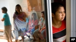 FILE PHOTO - Mariana Bulu, right, a former maid takes refuge at a temporary shelter for abused and mistreated maids before departing back to Indonesia at the Indonesian Embassy in Kuala Lumpur, Malaysia, Monday, July 2, 2007. (AP Photo/Marcus Yam)