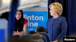 FILE - US Democratic presidential nominee Hillary Clinton talks to staff members, including aide Huma Abedin (L), on board her campaign plane in White Plains, New York, U.S. Oct. 28, 2016.