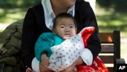 Seorang ibu mengasuh bayinya di sebuah taman di Beijing, China (30/10). China mengatakan kebijakan satu anak di negara itu masih tetap berlaku untuk saat ini.