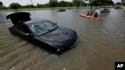 Domingo Molina paddles with his granddaughters down a flooded street in Houston, May 26, 2015.