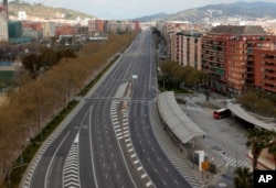 An empty avenue in Barcelona, Spain, Sunday, March 15, 2020. Spain's government announced Saturday that it is placing tight restrictions on movements and closing restaurants and other establishments in the nation. (AP Photo/Joan Mateu)