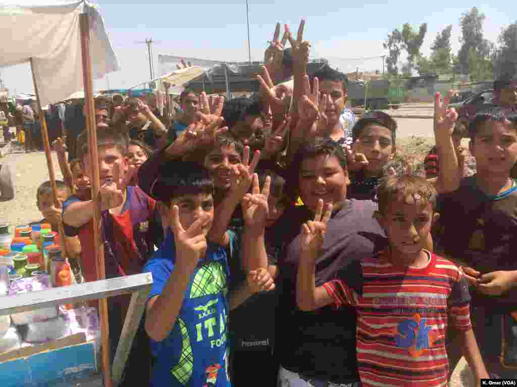 Children raise their hands, doing the V sign, in the Intisar neighborhood (left side of Mosul), July 19, 2017.