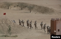 FILE - Pakistan Rangers walk with their weapons during a counterterrorism training demonstration on the outskirts of Karachi, Pakistan, Feb. 24, 2015.