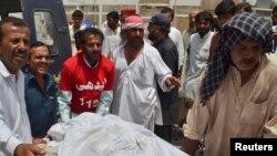 Petugas medis tengah memindahkan korban penembakan pria tak dikenal dari mobil ambulans ke ruang jenazah rumah sakit di Quetta, Pakistan (6/8). Sedikitnya 13 orang dikabarkan tewas dibunuh saat bus yang mereka tumpangi dalam perjalanan menuju propinsi Punjab.