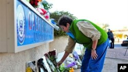 A woman leaves flowers outside the office of Congresswoman Gabrielle Giffords in Tucson, Arizona, 08 Jan 2011