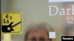 Наклейка на двери одного из магазинов сообщает, что наряду с латами, к оплате принимаются евро и доллары США. Рига, Латвия
