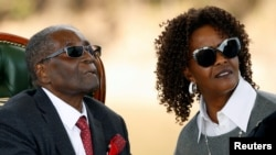 """Zimbabwe's former president Robert Mugabe and his wife Grace look on after addressing a news conference at his private residence nicknamed """"Blue Roof"""" in Harare, Zimbabwe, July 29, 2018."""
