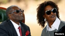 "FILE: Zimbabwe's former president Robert Mugabe and his wife Grace look on after addressing a news conference at his private residence nicknamed ""Blue Roof"" in Harare, Zimbabwe, July 29, 2018."