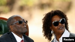 "FILE - Zimbabwe's former president Robert Mugabe and his wife Grace look on after addressing a news conference at his private residence nicknamed ""Blue Roof"" in Harare, Zimbabwe, July 29, 2018."