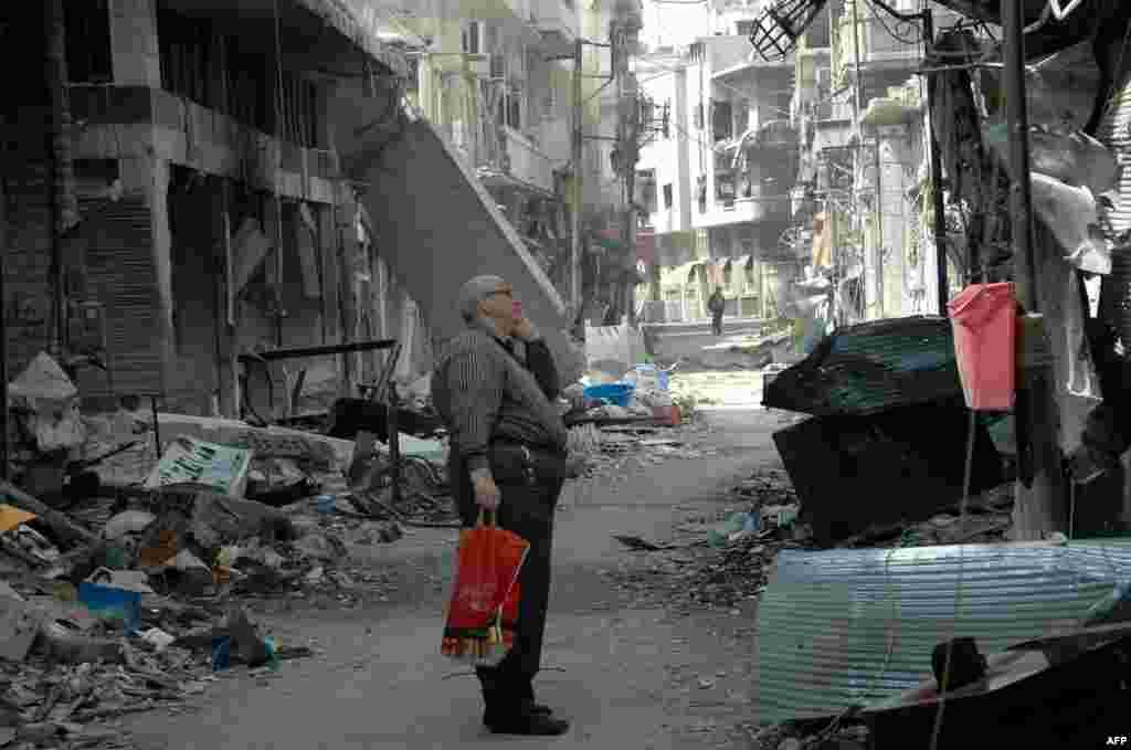 시리아 홈스에서 한 주민이 내전으로 파괴된 건물을 바라보고 있다. 반군은 한 때 거점이었던 홈스에서 정부군의 공세에 몰리자, 최근 철수했다.