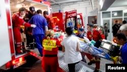 """Tim medis tengah menolong seorang korban kebakaran sebuah club malam di Bucharest, Romania (31/10). Sedikitnya 27 orang tewas dan 184 lainnya terluka akibat kebakaran saat berlangsungnya konser musik rock """"Goodbye to Gravity"""" di klub Colective di kota itu."""
