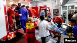"""Radnici hitne pomoći iznose jednog od povređenih u noćnom klubu """"Kolektiv"""" ispred bolnice u Bukureštu"""