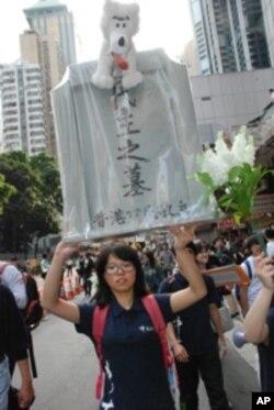香港中文大學社工系學生張同學高舉「香港民主之墓」標語參與遊行
