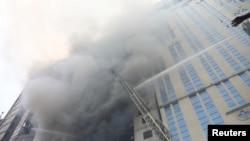 Petugas pemadam kebakaran berupaya memadamkan api yang menghanguskan bangunan berlantai 19 di kawasan komersial Banani di Dhaka, Bangladesh, Kamis 28 Maret 2019.