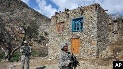 افغانستان میں امریکی انفنٹری کے دستے 16 فروری 2010ء کو ایک گاؤں کے پاس کھڑے ہیں جب کہ افغان شہری اوپر سے دیکھ رہے ہیں