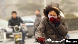 Una mujer usa máscara para desplazarse en su bicicleta en una calle de Beijing, donde la contaminación del aire es crítica con mucha frecuencia.