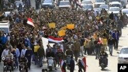 Waandamanaji wanaopinga serikali wakipita katika mitaa ya Cairo, Ijumaa Februari 11, 2011.