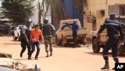 Tantara Mali membantu seorang sandera untuk meninggalkan lokasi serangan di hotel Radisson Blu di Bamako, Jumat (20/11).